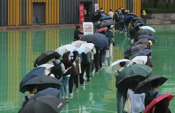지난달 24일 서울 성북구 서경대학교에서 열린 SK 그룹 상반기 공채 필기전형인 SK종합역량검사(SKCT)에서 우산을 쓴 수험생들이 거리를 두고 시험에 참석하기 위해 길게 줄을 서고 있다. 뉴스1