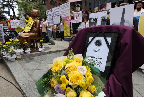 10일 오후 서울 종로구 옛 주한 일본대사관 앞에서 열린 '제1443차 일본군 위안부 피해자 문제해결을 위한 정기 수요시위'에 정의연 마포구 쉼터 '평화의 우리집' 소장 손모씨를 추모하는 액자와 꽃다발이 놓여져 있다. 연합뉴스