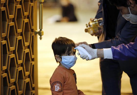 라마단 기간 중인 지난 5월 12일 이란의 테헤란 대학 내 모스크의 입구에서 병역 요원이 입장하려던 어린이의 체온을 재고 있다. 마스크 착용과 체온 재기, 손씻기는 전 세계에서 공통적으로 활용되는 방역 활동이다. 이란에선 이런 노력에도 2차 대유행이 한창이다. EPA=연합뉴스