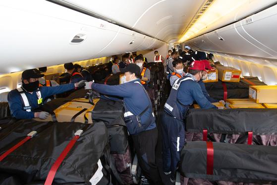 대한항공 직원들이 11일 오전 10시40분 인천공항을 출발해 미국 시카고로 향하는 여객기 KE037편에 카고시트백(Cargo Seat Bag)을 장착하고 있다.  카고시트백은 기내 좌석에 짐을 실을 수 있도록 특별 포장된 별도의 가방을 말한다. 이날 대한항공은 카고시트백을 통해 마스크 167만장을 운송했다. 사진 대한항공