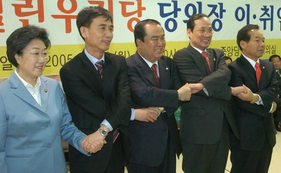 2005년 4월 열린우리당 전당대회에서 선출된 문희상(가운데) 의장 취임식에서 한명숙(왼쪽) 의원과 유시민(왼쪽 둘째) 의원이 손을 맞잡고 있다. [중앙포토]