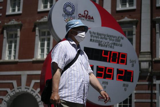 도쿄 시민이 10일 마스크를 쓰고 거리를 지나고 있다. 뒤로 올림픽까지 남은 날 수(D-408일)를 가리키는 시계가 보인다. [AP=연합뉴스]