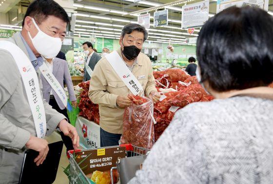 지난 9일 서울 농협하나로마트 양재점에서 열린 '태안 마늘 대도시 직판행사'에서 가세로 태안군수(가운데)가 매장을 찾은 고객에게 마늘을 판매하고 있다. [사진 태안군]