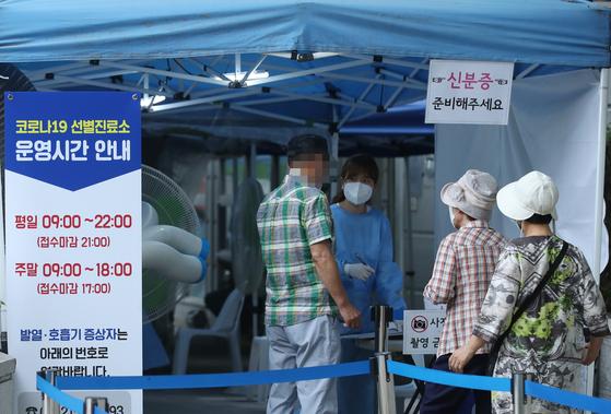 12일 오후 서울 서초구보건소에 마련된 선별진료소에서 시민들이 신종 코로나바이러스 감염증(코로나19) 검사를 받기 위해 줄 서 있다. 연합뉴스