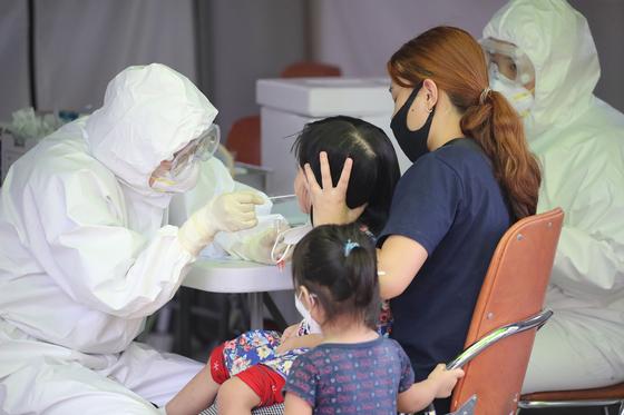 11일 오후 대구 달서구보건소에 마련된 선별진료소에서 방호복을 입은 의료진이 신종 코로나바이러스 감염증(코로나19) 검사를 위해 방문한 가족의 검체를 채취하고 있다. 뉴스1