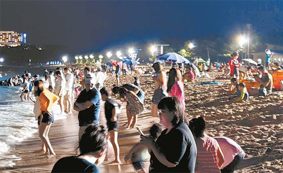 지난해 강원 동해안 최초로 야간 개장한 속초해수욕장 모습. 대형 조명시설이 생기면서 야간 수영이 가능해지자 오후 8시가 넘은 시간까지 피서객들이 물놀이를 즐기고 있다. 중앙포토