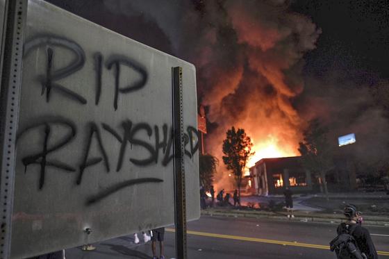12일(현지시간) 아프리카계 미국인 레이샤드 브룩스가 조지아주 애틀란타에서 경찰의 총에 맞아 숨지는 사건이 발생했다. 사건이 발생한 웬디스 매장이 불에 타고 있고, 표지판에는 숨진 레이샤드를 추모하는 글이 적혀있다. [AP=연합뉴스]