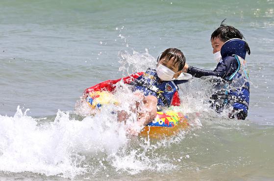 본격적인 피서철을 앞두고 정부가 해수욕장 혼잡도를 미리 확인할 수 있는 시스템 개발을 검토하고 있다. 사진은 7일 부산 해운대해수욕장을 찾은 어린이가 마스크를 착용한 채 물놀이를 하는 모습. 송봉근 기자