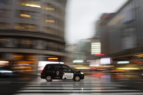코로나19로 본업이 어려워진 일본 택시 5대 중 1대가 음식배달업에 뛰어들었다. 사진은 지난해 11월 22일 도쿄의 택시회사 니혼교통 소속 택시가 도쿄 긴자 거리를 주행하는 모습. 이 회사는 한 고급 스테이크 식당과 계약을 맺고 음식을 배달한지 열흘만에 1200만엔(약 1억3400만원)의 매상을 올렸다. [AP=연합뉴스]