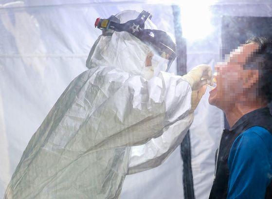 광주광역시 서구보건소 의료진이 레벨D 방호복을 입고 시민의 검체 채취를 하고 있다. 광주=프리랜서 장정필