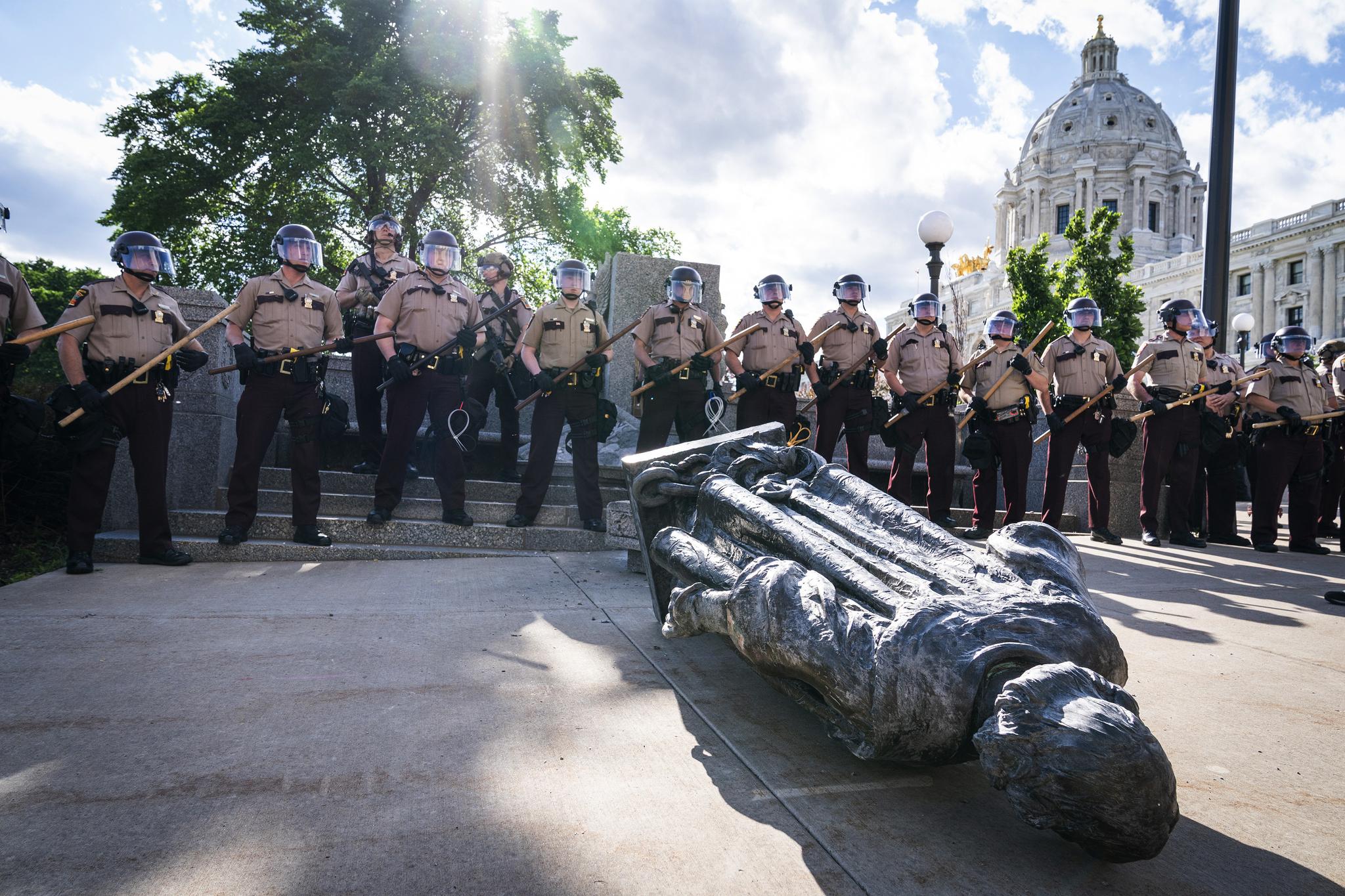 10일(현지시간) 인종차별 반대 시위대가 강제로 끌어내린 크리스토퍼 콜럼버스 동상 뒤로 미네소타주 경찰관들이 줄지어 서 있다. AP=연합뉴스