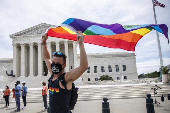 15일(현지시간) 미국 대법원이 동성애자나 트랜스젠더라는 이유로 해고될 수 없다면서 고용 차별을 금지하는 판결을 내리자 한 성소수자 지지자가 '프라이드 플래그'(성소수자의 인권을 상징하는 무지개 깃발)를 펼쳐 들고 있다. [EPA=연합뉴스]