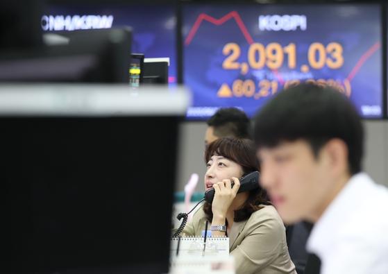 코스피가 3% 안팎 반등하면서 출발한 16일 오전 서울 중구 하나은행 본점 딜링룸에서 직원이 업무를 보고 있다. 연합뉴스