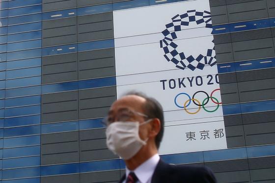 마스크를 쓴 채 도쿄올림픽 배너 앞을 지나는 도쿄시민. 로이터