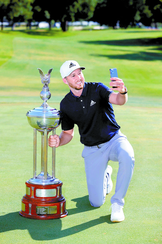 9년 전 출시됐던 아이언을 앞세워 PGA투어 대회에서 우승한 버거. 찰스 슈왑 챌린지 트로피 옆에서 셀카를 찍고 있다. [AFP=연합뉴스]