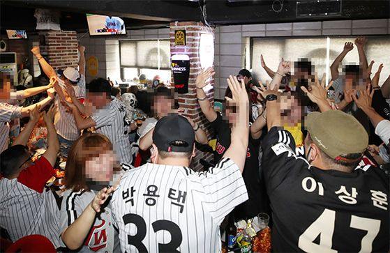 야구 팬은 무관중 경기로 진행되는 KBO리그를 각자의 방식으로 즐기고 있다. 지난달 5일 정규시즌 개막전 당시 LG 팬들이 서울의 한 식당에 모여 응원하는 모습. [연합뉴스]