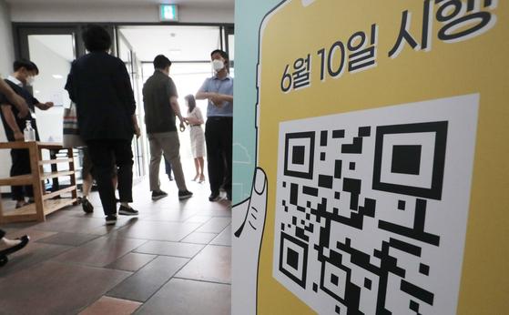 14일 오전 서울의 한 성당에서 교인들이 예배에 참석하기 위해 전자출입명부(QR코드)를 찍고 있다. 15일부터 수도권 학원도 QR코드 기반 전자출입명부 설치가 의무화됐다. 뉴스1