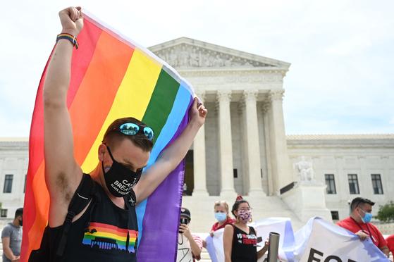 15일(현지시간) 미국 워싱턴D.C의 연방대법원 앞에서 한 남성이 성소수자 인권운동을 상징하는 무지개색 깃발을 들고 있다. [AFP=연합뉴스]