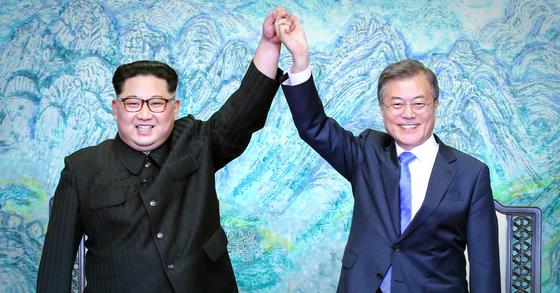 문재인 대통령(오른쪽)과 김정은 북한 국무위원장이 2018년 4월 27일 오후 판문점 평화의 집에서 열린 남북정상회담에서 한반도의 평화와 번영, 통일을 위한 판문점 선언문에 서명 후 서로 손을 잡고 위로 들어보이고 있다. [청와대사진기자단]