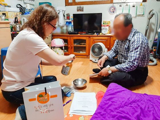 광진구보건소 치매안심프로그램 담당자가 치매를 앓는 노인을 찾아 인지능력 향상 프로그램의 일부인 버섯 수확 방법 등을 알려주고 있다. [사진 광진구]