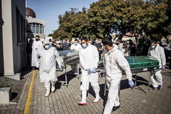 남아프리카공화국 케이프타운에서 장의사들이 코로나19 사망자들의 관을 옮기고 있다. [AFP=연합뉴스]