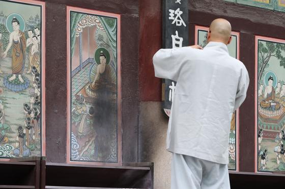 19일 오전 서울 종로구 견지동 조계사 대웅전에서 한 스님이 불에 탄 대웅전 외벽을 살펴보고 있다. 뉴스1