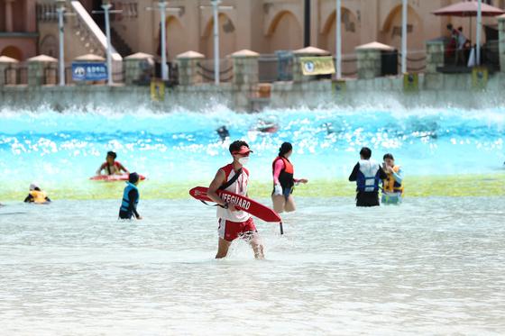 무더위에 워터파크를 찾은 피서객들의 모습. 코로나19의 여파로 '물 반 사람 반'이던 예년의 풍경은 사라졌다. 마스크를 착용한 안전 요원의 모습도 아직은 낯설다. [사진 에버랜드]