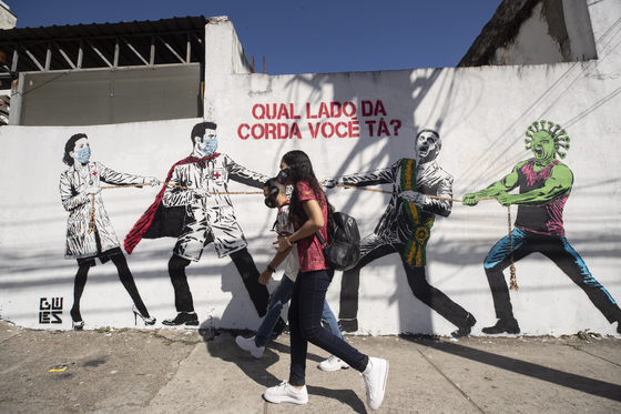 19일(현지시간) 브라질 상파울루의 한 거리. 벽에는 의인화된 코로나19 캐릭터와 자이르 보우소나루 브라질 대통령에 맞서 줄다리기를 하고 있는 의료진의 모습이 그러져 있다. AP=연합뉴스