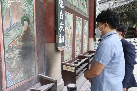 지난 19일 오전 서울 종로구 견지동 조계사 대웅전에서 조계종 관계자가 불에 탄 대웅전 외벽 벽화 일부를 살펴보고 있다. 뉴스1
