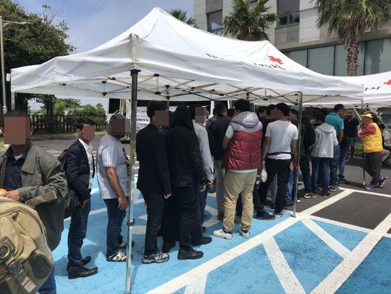 2018년 제주 출입국·외국인청 앞마당에 마련된 대한적십자사 의료봉사 부스에 몰린 예멘 난민 신청자. 건강검진 차례를 기다리고 있다. 최충일 기자