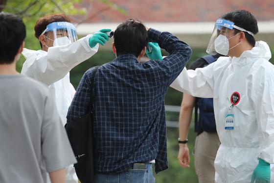 20일 오전 2020년도 대구시 소방공무원 채용 필기시험이 치러지는 대구 수성구 정화중학교에서 보호복을 입은 시험관리본부 요원들이 신종 코로나바이러스 감염증(코로나19) 예방을 위해 응시자 앞뒤 간격을 유지한 채 발열 검사를 하고 있다. 뉴스1