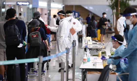 지난 20일 오후 인천국제공항 제2여객터미널에서 네덜란드 암스테르담 등에서 온 입국자들이 방역 관계자의 안내를 받으며 입국장을 빠져나가고 있다. 이날 국내 코로나19 해외유입 감염 사례는 31명이다. 연합뉴스