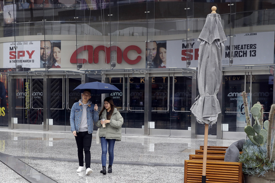 지난 3월 코로나19 확산에 따라 셧다운에 들어간 미국 LA의 AMC 앞에 서 있는 관객들 모습. AMC는 미국 최대 영화관 체인이다. [AP=연합뉴스]
