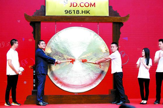 알리바바에 이은 중국 2위 온라인 쇼핑몰 징둥그룹은 지난 18일 홍콩 증시에 2차 상장하며 기업 공개(IPO)에 성공했다. 증시 입성을 알리는 징을 치고 있는 징둥닷컴 관계자들. [신화=연합뉴스]