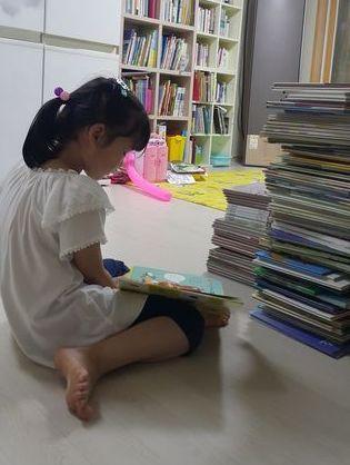 옆집에서 선물받은 그림책을 읽고 있는 은지. [사진 배은희]