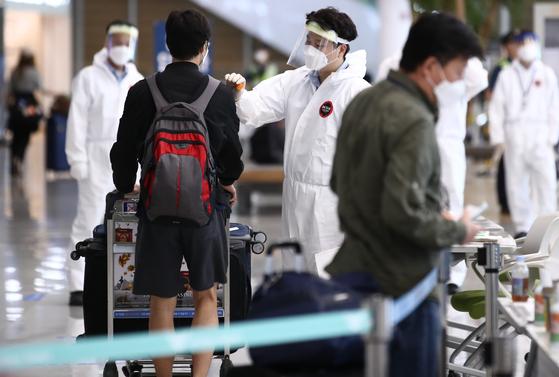 20일 오후 인천국제공항 제2여객터미널에서 해외 입국자들이 방역 관계자의 안내를 받으며 입국장을 빠져나가고 있다.   연합뉴스