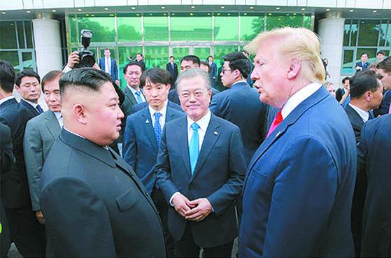 도널드 트럼프 대통령과 김정은 국무위원장이 지난해 6월 30일 판문점에서 대화하고 있다. 문재인 대통령이 이를 바라보고 있다. [뉴시스]