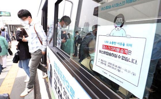 대중교통 이용 때 마스크 착용 의무화 시행 첫날인 지난달 26일 오전 서울역 환승센터에서 시민들이 마스크를 쓰고 버스를 이용하고 있다. 연합뉴스