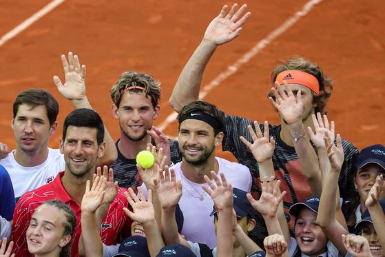 지난 13일 조코비치가 기획한 미니 테니스 투어 대회에서 다른 톱 랭커들과 볼 키즈들이 마스크를 쓰지 않고 바로 옆에 붙어서 기념 사진을 찍고 있다. [로이터=연합뉴스]