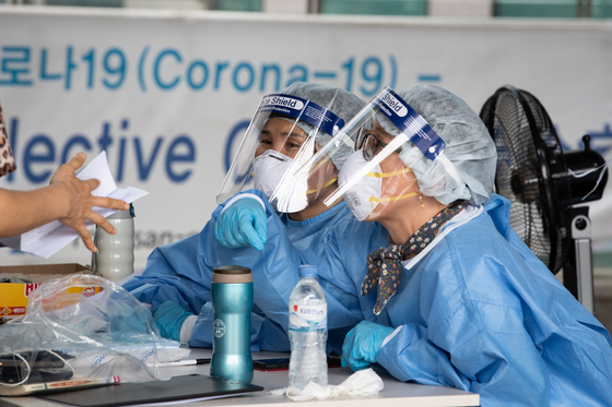23일 서울시내 한 신종 코로나바이러스 감염증(코로나19) 선별진료소에서 방역복을 착용한 관계자들이 업무를 보고 있다. 뉴스1