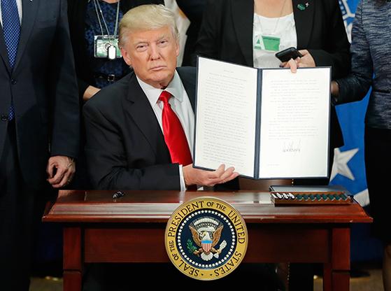 2017년 1월 반이민 행정명령에 사인하고 이를 들어 보이는 도널드 트럼프 미국 대통령. [AP=연합뉴스]