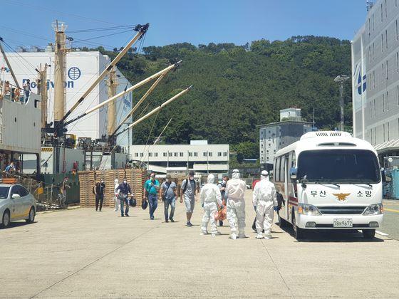 23일 낮 부산 감천항에 정박중인 러시아 선박에서 코로나19 확진판정을 받은 러시아 선원들이 부산의료원에서 입원치료를 받기 위해 이송되고 있다. 송봉근 기자