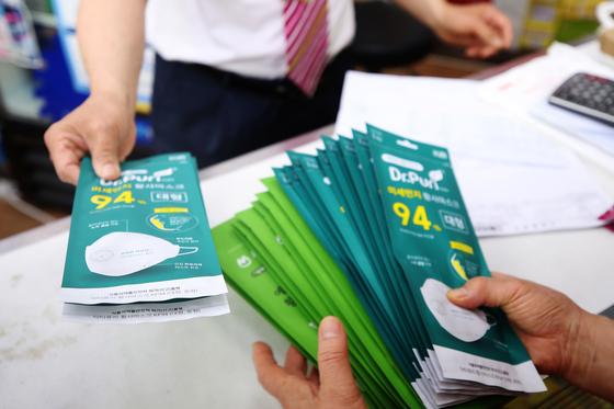 18일 오전 서울 종로구의 한 약국에서 시민이 공적 마스크를 구매하고 있다. 연합뉴스