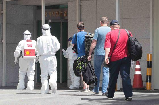 23일 낮 코로나19 확진판정을 받은 러시아 선원들이 부산 감천항에서 이송돼 부산의료원에 들어가고 있다. 송봉근 기자