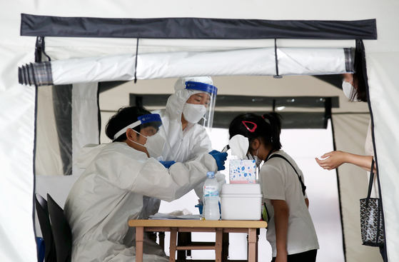 22일 광주 북구보건소 선별진료소에서 의료진이 신종 코로나바이러스 감염증(코로나19) 검사를 받는 학생의 체온을 측정하고 있다. 연합뉴스