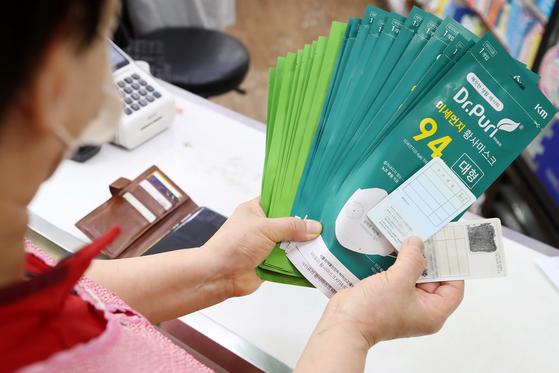 지난 18일 오전 서울 종로구의 한 약국에서 시민이 공적 마스크를 구매하고 있다. 식품의약품안전처에 따르면 이날부터 공적 판매처에서 일주일에 1인당 10장씩의 공적 마스크를 살 수 있다. 연합뉴스.