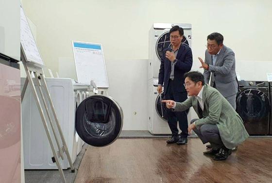 이재용 삼성전자 부회장(가운데)이 23일 수원 생활가전사업부를 찾아 이재승 생활가전사업부장(오른쪽·부사장), 이기수 생활가전개발팀장(왼쪽·전무)과 함께 AI 세탁기를 살폈다. AI는 그가 지속해서 강조한 차세대 성장동력이다. [사진 삼성전자]