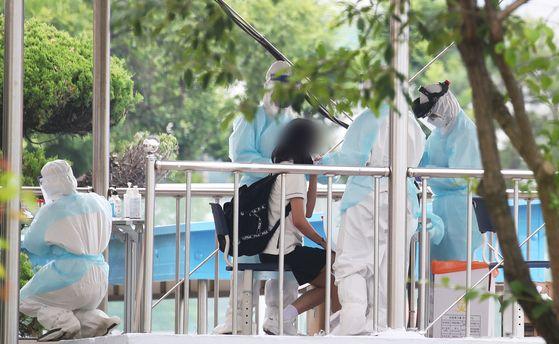 1학년 학생 한 명이 신종 코로나바이러스 감염증(코로나19) 확진 판정을 받은 경기도 시흥시 정왕중학교에서 12일 오후 의료진이 학생들 검체 채취를 하고 있다.연합뉴스