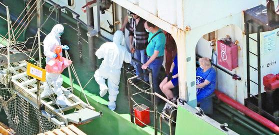 23일 오후 부산 감천항에 정박 중인 러시아 국적 냉동 화물선에서 코로나19 양성 판정을 받은 선원들이 부산의료원으로 이송되고 있다. 이 화물선 선원 21명 중 16명이 양성판정을 받았다. 송봉근 기자