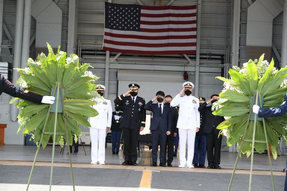유해 인수식에서 한국과 미국의 참석자들이 한국군 유해를 향해 경례하고 있다. [사진 국방부]